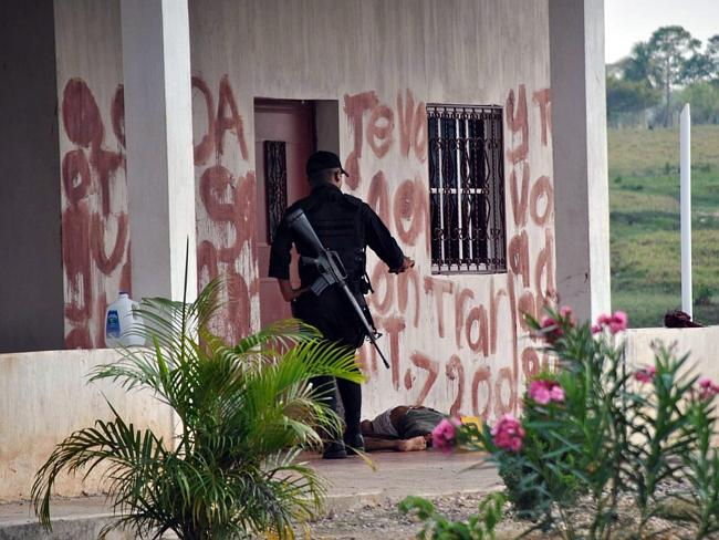 Members of the security forces in Guatemala observe words written in blood on the walls of a house next to the bodies of 26 men and two women. Police sources said the victims allegedly were shot dead and beheaded by the Mexican cartel Los Zetas.