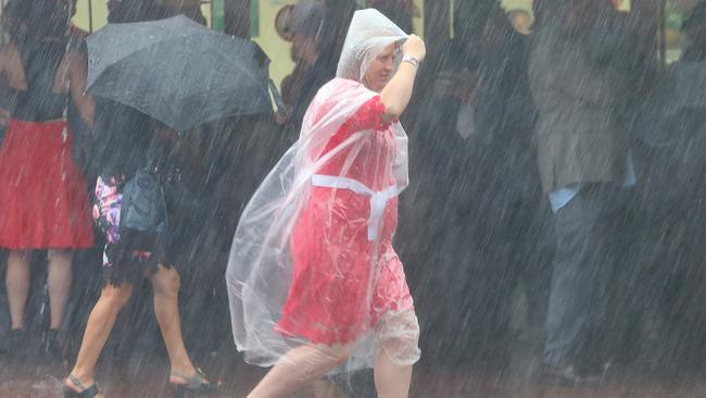 Drenched ... Oaks Day racegoers run for cover as rain lashes Flemington. Picture: Ian Currie