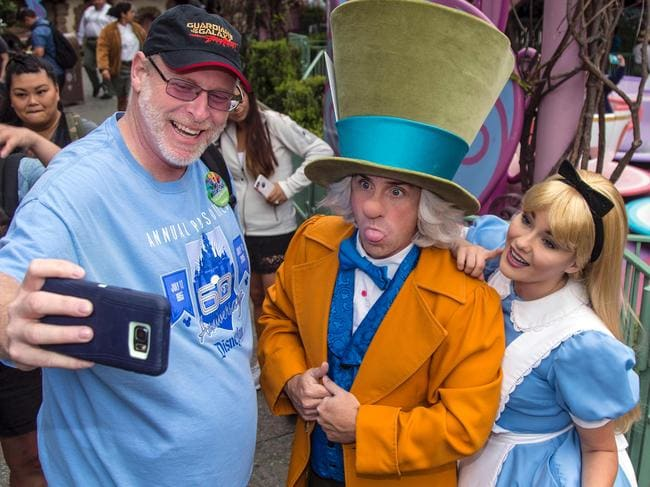 "This photo courtesy of Disney shows Huntington Beach, California, resident Jeff Reitz snaps a selfie with The Mad Hatter and Alice after a teacup ride at the Mad Tea Party in Fantasyland at Disneyland on June 22, 2017, during his 2,000th visit to the park in Anaheim, California.  As one of the world's largest entertainment companies, Disney is used to adoring fans, but Reitz has topped them all, visiting its California theme park 2,000 days in a row. Reitz marked the milestone on June 22, using his Disneyland Resort annual pass which had enabled his trek to the park on a daily basis since January 1, 2012. ""What we mostly known about him is that he loves Disneyland,"" said John McClintock, a spokesman for the theme park.  / AFP PHOTO / © Disney 2017 - All Rights Reserved / Joshua SUDOCK / TO GO WITH AFP STORY,  US-Disneyland-offbeat = RESTRICTED TO EDITORIAL USE - MANDATORY CREDIT ""AFP PHOTO / Disney / Joshua SUDOCK"" - NO MARKETING NO ADVERTISING CAMPAIGNS - DISTRIBUTED AS A SERVICE TO CLIENTS"