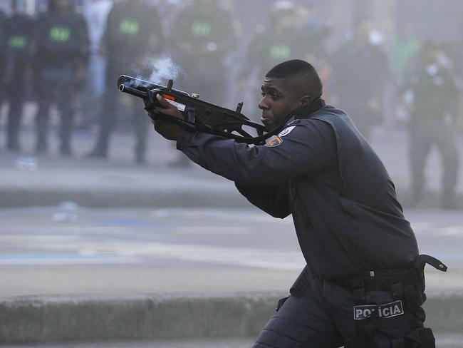 A police officer aims his weapon during clashes with anti-World Cup demonstrators near Maracana Stadium.