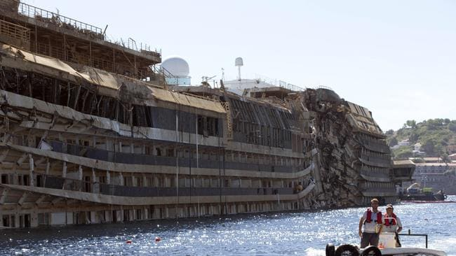Dwarfed ... a small boat passes next to the damaged side of the <i> Costa Concordia </i>on the Tuscan island of Giglio, Italy. Picture: Andrew Medichini