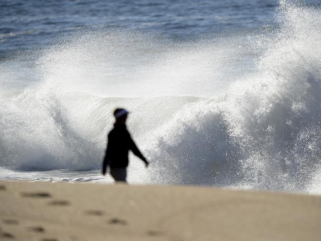 An early morning walker, near the notorious shore break. Picture: Peter Clark