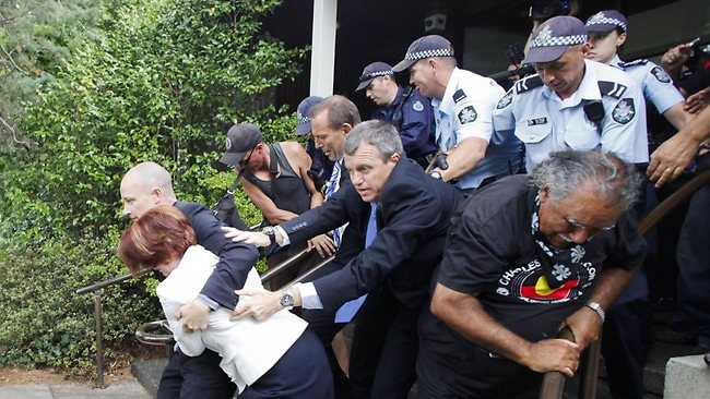 Prime Minister Julia Gillard rushed to safety by police and bodyguards. (AAP Image/Lukas Coch)