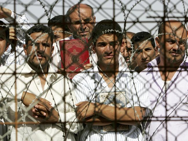 Iraqi prisoners stand inside the Abu Ghraib prison compound, shortly before they are released in 2006. Pic: AFP.