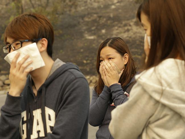 Vincent Yeoh, from left, Ai Peng, Estella Fong, all from Malaysia, cover their mouths from smoke. Picture: AP