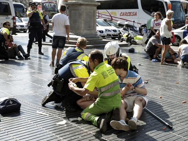 Medics and police tend to injured people near the scene of a terrorist attack in the Las Ramblas area in Barcelona, Spain. Picture: Getty