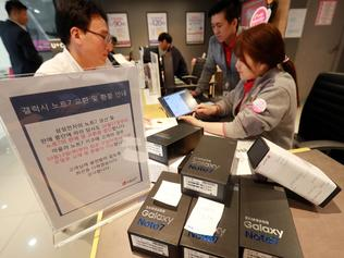 Customers return their Samsung Note 7 mobile phones at a dealership in Seoul on October 13, 2016. South Korea's central bank cut its growth outlook for next year to 2.8 percent in the wake of Samsung Electronics' damaging recall crisis and its impact on the economy. / AFP PHOTO / YONHAP / yonhap / REPUBLIC OF KOREA OUT NO ARCHIVES RESTRICTED TO SUBSCRIPTION USE