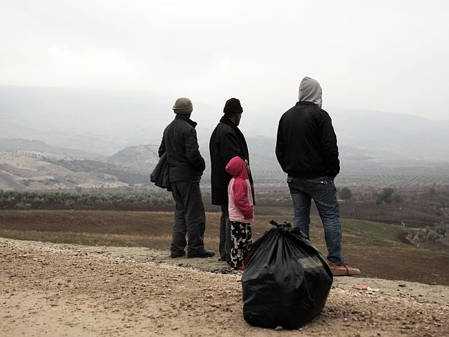 A Syrian family newly arrived in Turkey look at the Syrian border from the Turkish side on January 14, 2014 in Kilis.
