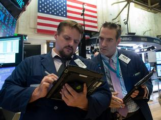 Traders work on the floor at the closing bell of the Dow Industrial Average at the New York Stock Exchange on August 16, 2017 in New York. Wall Street stocks rose early Wednesday ahead of the release of Federal Reserve meeting minutes expected to shed light on the prospects of another interest rate increase in 2017. / AFP PHOTO / Bryan R. Smith