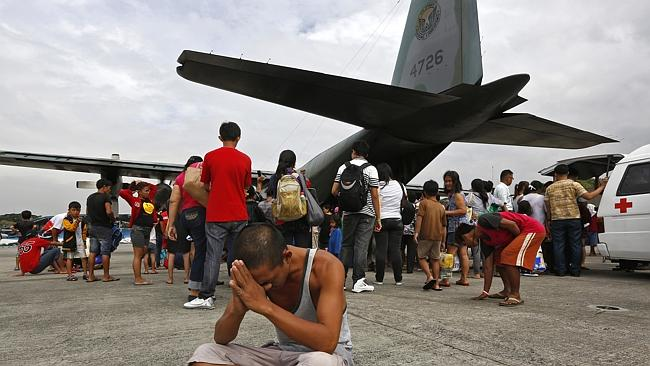 A survivor from Tacloban, which was devastated by Typhoon Haiyan gestures while sitting on the ground after disembarking a Phili