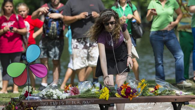 "Tributes grow ... a woman places flowers on a fan memorial in honor of Robin Williams on the bench made famous by his movie ""Good Will Hunting"" in Boston Public Garden. Picture: Getty Images"
