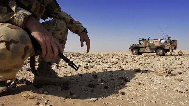 An Australian soldier squats while a Bushmaster Infantry Mobility Vehicle is at halt during a desert reconnaissance patrol south of As Samawah in Iraq.