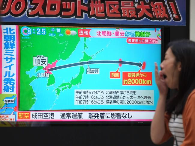 Pedestrians look at a television screen broadcasting a news report in Tokyo today following a North Korean missile test that passed over Japan. Picture: AFP