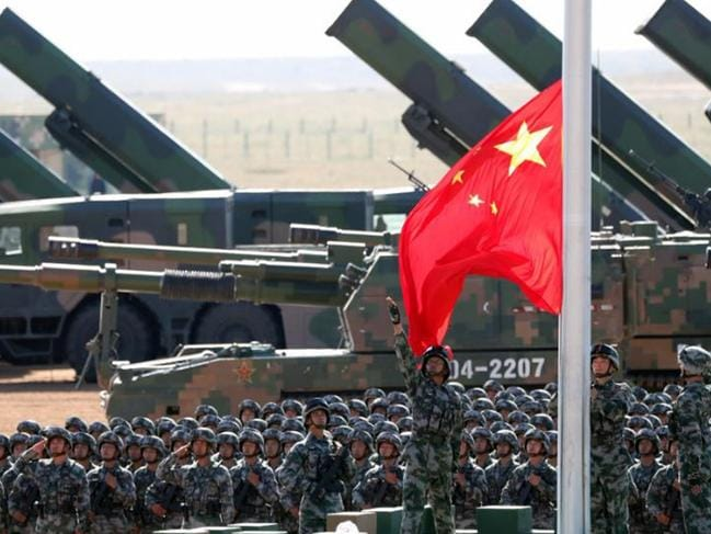 In this photo released by China's Xinhua News Agency, Chinese People's Liberation Army (PLA) troops perform a flag raising ceremony Sunday, July 30, 2017 for a military parade to commemorate the 90th anniversary of the founding of the PLA on Aug. 1 at Zhurihe training base in north China's Inner Mongolia Autonomous Region. (Pang Xinglei/Xinhua via AP)