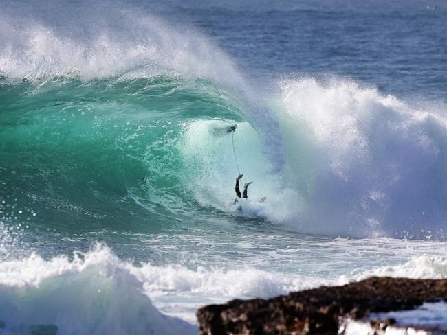 RVaculik wipes out near the rocks during the Red Bull Cape Fear surfing event at Cape Solander, Sydney. Picture: Brett Costello