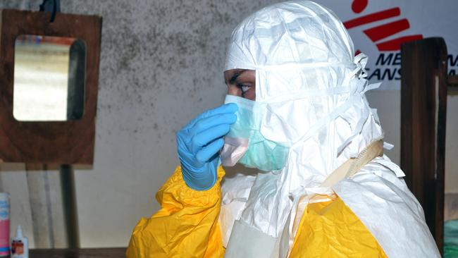 Helping patients ... a member of Médecins Sans Frontières (MSF) puts on protective gear at the isolation ward of the Donka Hospital in Conakry. Picture: Cellou Banani