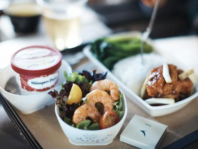 Happily polish off all the ice cream you're given, because any unopened tubs will go straight in the bin. (Pictured: Premium economy meal on Cathay Pacific.)