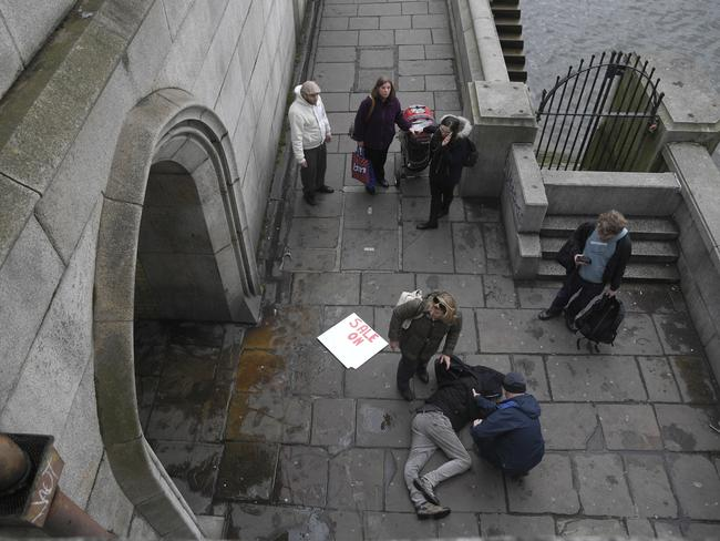 An injured man is assisted on the footpath under Westminster Bridge. Picture: Reuters