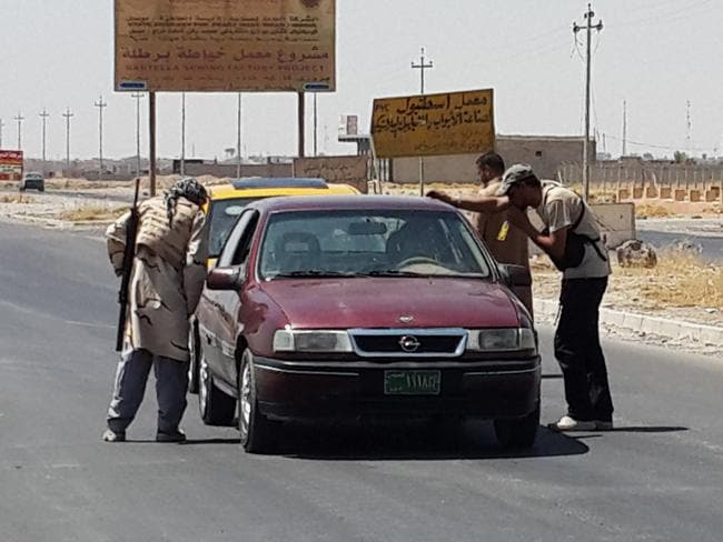 Blockade ... Islamic State group militants and Tribal fighters take control of a checkpoint that used to be controlled by Kurdish Peshmerga fighters, as people leave a village outside Irbil, northern Iraq. Source: AP