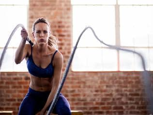Girl doing fitness workout with ropes in gym