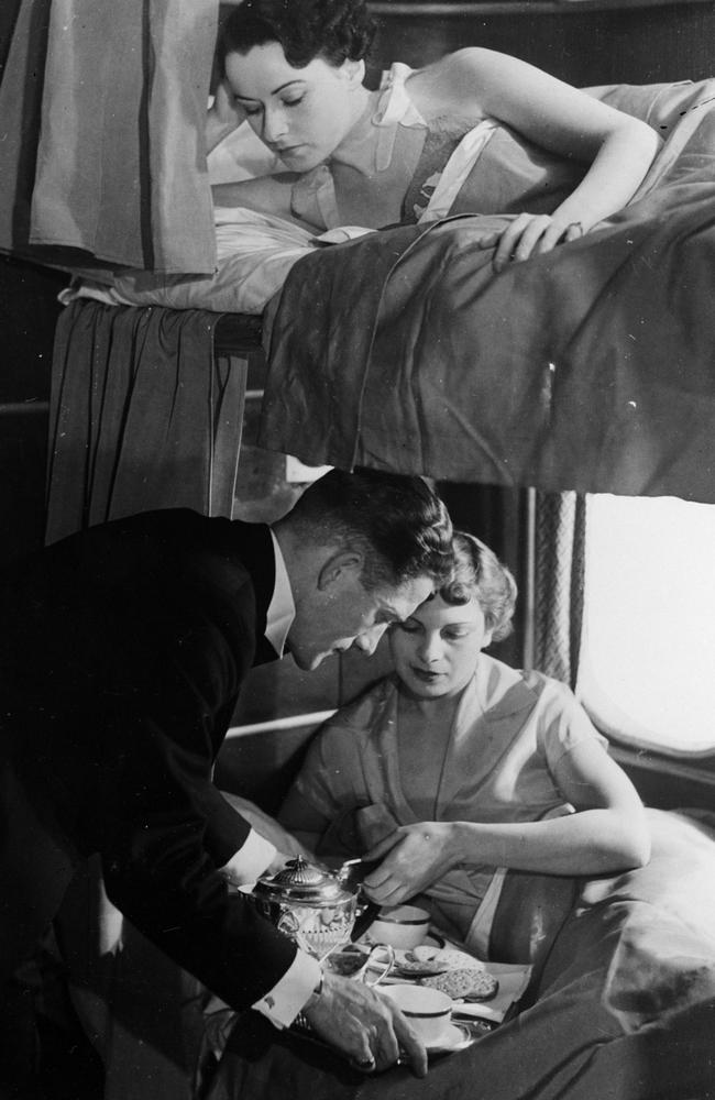 A steward aboard the giant flying-boat, 'Canopus' serves breakfast to a passenger in a lower bunk. The Canopus could cruise at 200mph and carried 16 passengers in night stages. Photo: General Photographic Agency/Getty Images