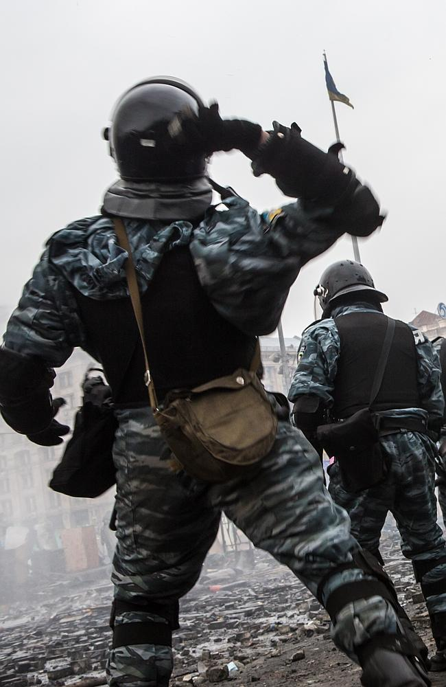 Riot police throw stones at anti-government protesters, who are throwing rocks in return.