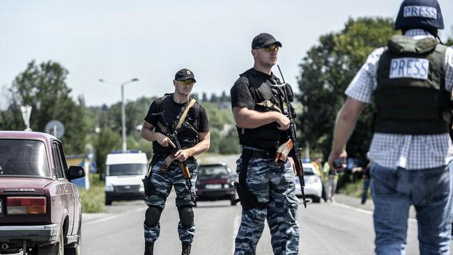 Difficult conditions ... pro-Russian militants block the road behind Dutch and Australian forensic teams on their way to the crash site of Malaysia Airlines flight MH17. Picture: Bulent Kilic