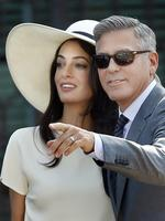George Clooney, right, flanked by his wife Amal Alamuddin, arrives at the Cavalli Palace for the civil marriage ceremony in Venice, Italy on Monday, September 29th 2014. Picture: AP