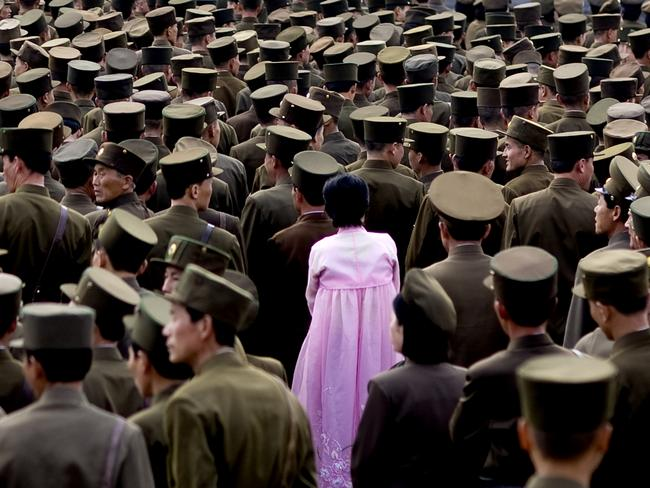 A woman standing in the middle of a crowd of soldiers. This picture is not supposed to be taken as officials do not allow army pictures.