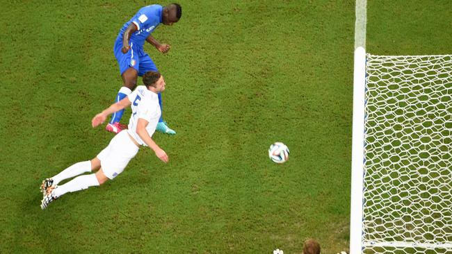 Italy's Mario Balotelli, top, scores his side's winning goal.