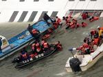This photo taken at sea some 20 kilometres off the island of Byungpoong in Jindo on April 16, 2014 shows South Korea Coast Guard members rescuing some of the 477 passengers and crew aboard a South Korean ferry capsizing on its way to Jeju island from Incheon. Picture: AFP