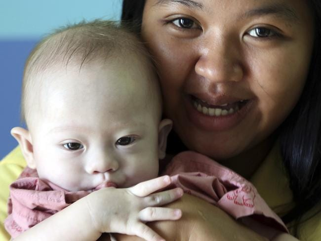The Gammy saga ... Thai surrogate mother Pattaramon Chanbua, a 21-year-old food vendor, with Gammy, a nine-month old baby boy who was born with Down syndrome. Picture: AP