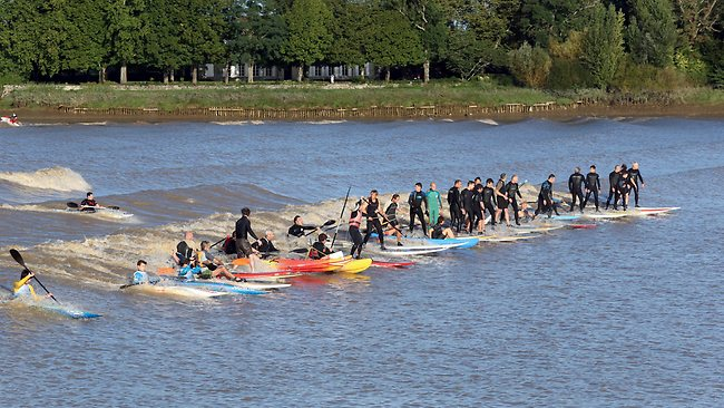 "People surf the ""mascaret"", a tidal wave on the Dordogne river, at Saint-Pardon-de-Vayres, southwestern France. The ""mascaret"" is a tidal phenomenon that occurs in the mouth and the lower reaches of some rivers when their power is upset by the flow of the tide. Picture: Nicolas Tucat"