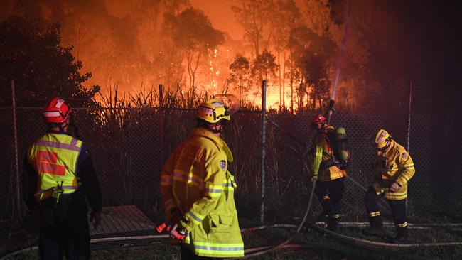 Firefighters fight flames close to homes in Corryton Court, Wattle Grove. Picture: AAP