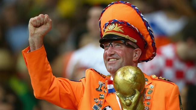 A Netherlands fan poses with a replica of the World Cup trophy during the 2014 FIFA World Cup Brazil.