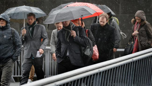 Commuters struggle into work through the cold wet weather in Melbourne. Picture: Nicole Garmston