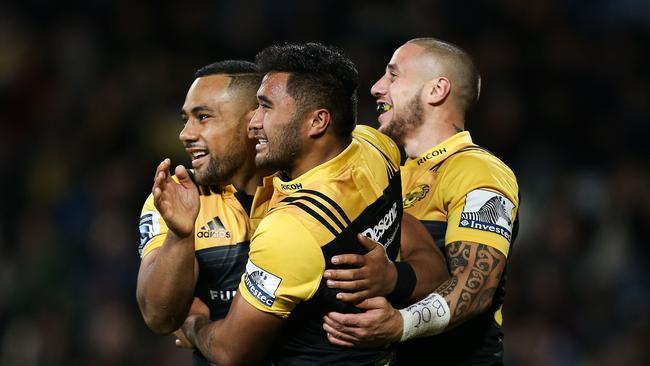 Vince Aso of the Hurricanes celebrates a try with teammates TJ Perenara and Ngani Laumape.