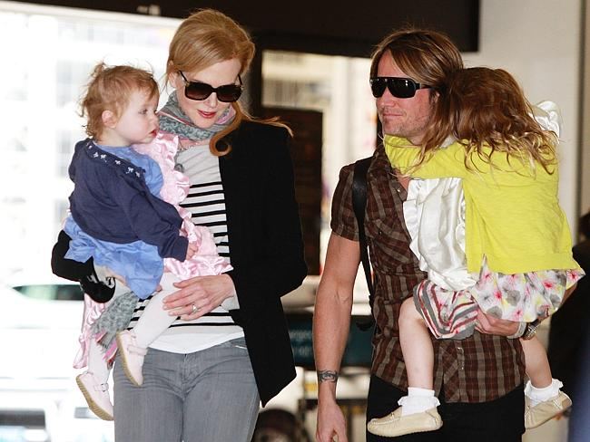 Nicole Kidman holding daughter Faith and singer husband Keith Urban holding eldest daughter Sunday Rose walk through Sydney International Airport in Sydney.