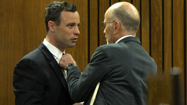 In court ... Oscar Pistorius has his tie adjusted by his uncle Arnold Pistorius, right, in court during his ongoing murder trial in Pretoria today. Picture: Herman Verwey