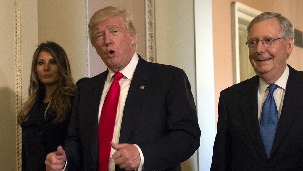 President-elect Donald Trump, accompanied by his wife Melania, and Senate Majority Leader Mitch McConnell gestures while walking on Capitol Hill in Washington. Picture: Molly Riley/AP