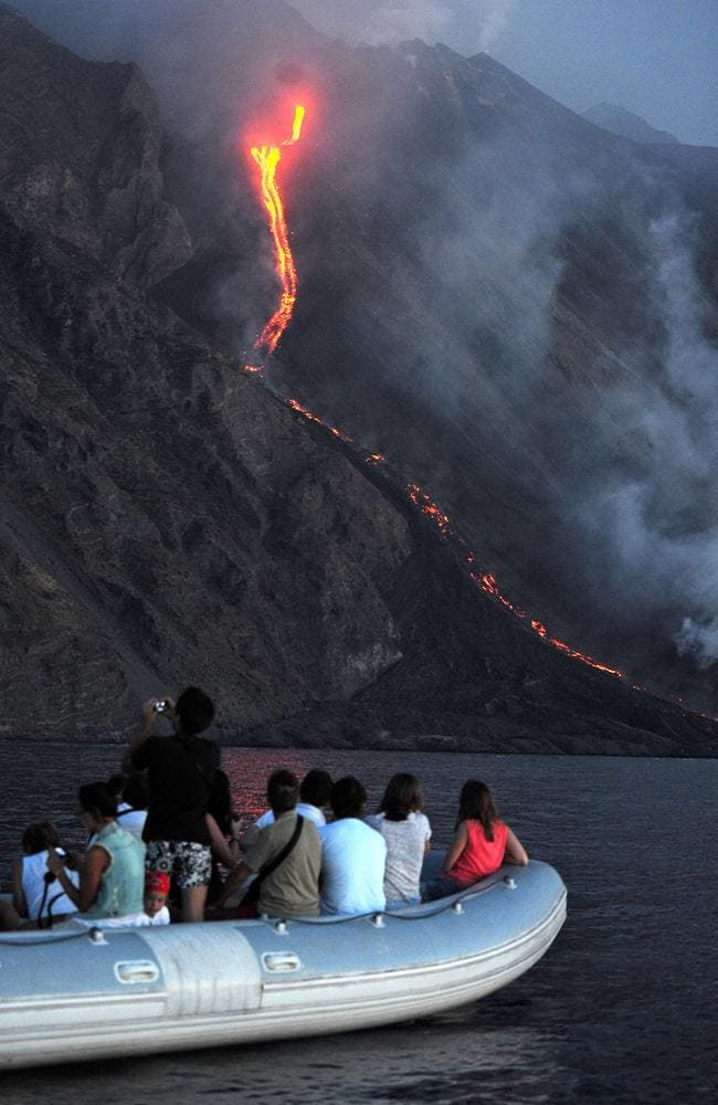 A boat of tourists watches as lava from the Stromboli volcano flows into the sea. Picture: AFP