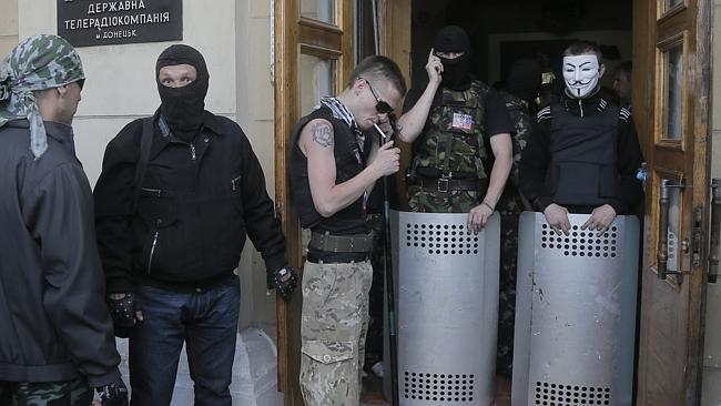 Siege ... masked pro-Russian activists guard the entrance after storming a regional Telev