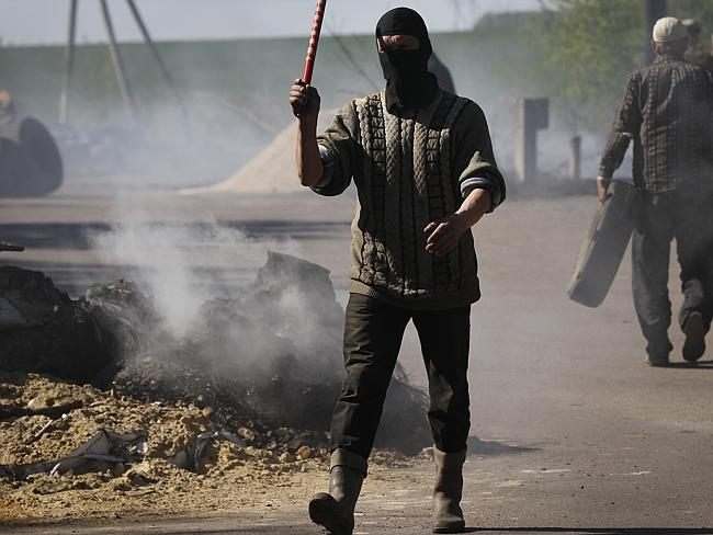 Standing firm... A pro-Russian militant directs traffic at a checkpoint following the att
