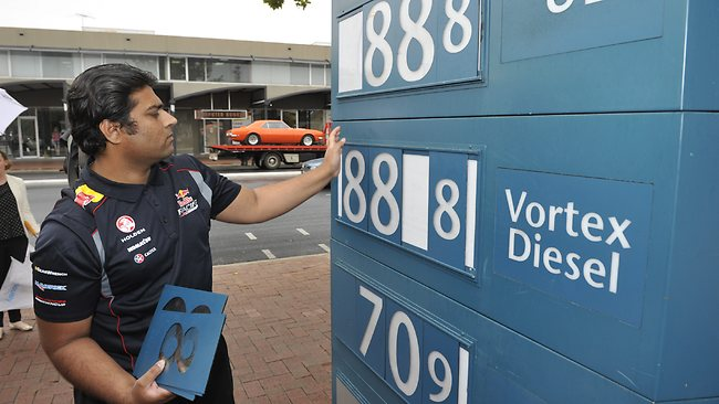 Caltex store manager Tahir Ali changes the signs to 88.8c per litre. Picture: Campbell Brodie