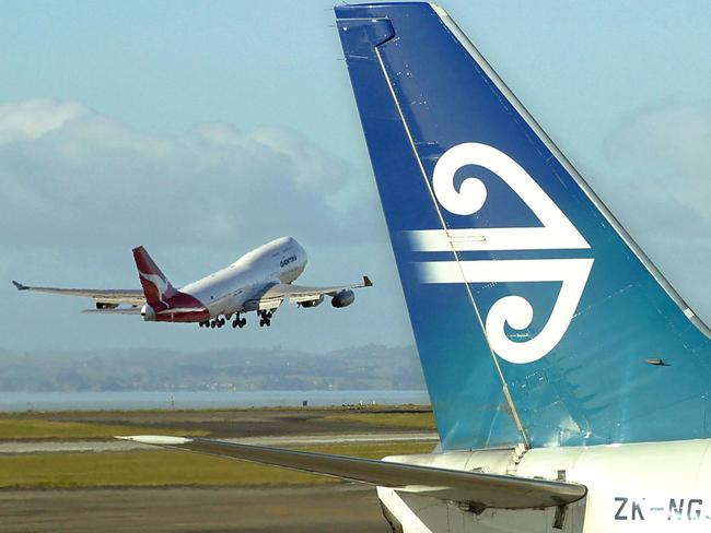 (FILES) This file photo taken on December 5, 2003 shows an Air New Zealand Boeing 737 sitting at a departure gate while an Australian Qantas Boeing 747-400 takes-off from Auckland Airport in Auckland. Thousands of airline passengers were stranded in Auckland on September 18, 2017 after a pipeline leak cut jet fuel supplies to New Zealand's largest airport, forcing planes to remain grounded, authorities said. / AFP PHOTO / Dean TREML