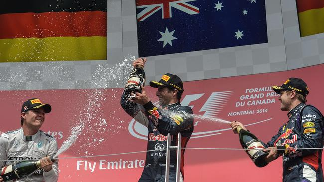 Ricciardo gets a champagne shower from Rosberg and Vettel.