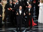 "'La La Land' producer Fred Berger speaks at the microphone with producer Marc Platt as production staff consult behind them regarding a presentation error of the ""Best Picture"" award (later awarded to 'Moonlight') onstage during the 89th Annual Academy Awards. Picture: Getty"