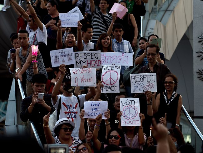 United stand ... anti-coup protestors hold placards during a protest in downtown Bangkok.
