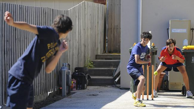 Ashton Agar bowls to his brothers Will and Wesley at the Agar family home in Melbourne in 2010. Picture: Hilton Stone