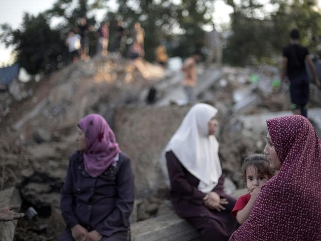 Reduced to rubble ... family members sit on the remains of their destroyed house following an Israeli missile strike. Picture: Khalil Hamra